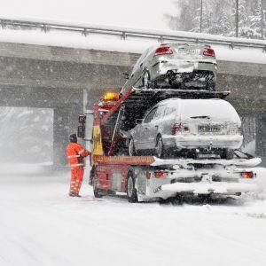 Kolaroituja autoja nostetaan hinausauton kyytiin lumisateessa moottoritiellä.