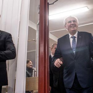 Kävelykepin kanssa kulkeva Zeman on tulossa ovesta sisään hymyillen leveästi. Ympärillä on tummapukuisia turvamiehiä.