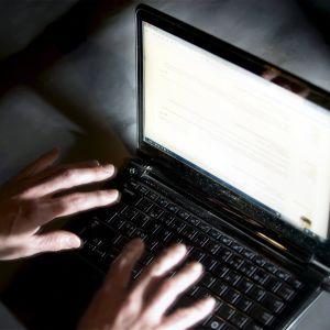 Mies kirjoittaa kannettavalla tietokoneella.