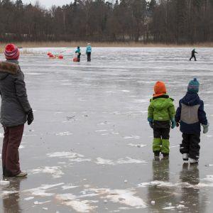 Ihmisiä järven jäällä.