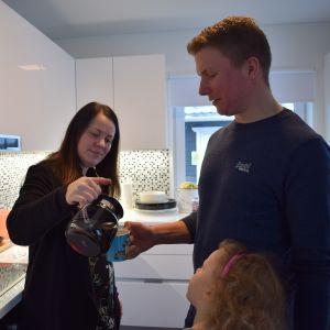 Perheen äiti kaataa kahvia isälle.