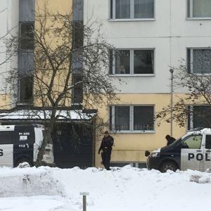Kaksi poliisin pakettiautoa kerrostalon edessä