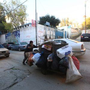 YK:n palestiinalaispakolaisten avustusjärjestön UNRWA:n työntekijä työntää roskakärryä Balatan pakolaisleirillä Länsirannalla tammikuun alussa.