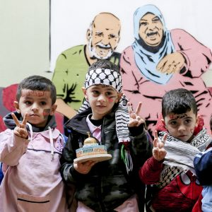 Palestiinalaislapset poseeraavat UNRWA:n koulussa.