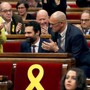 Roger Torrent istuu parlamenttisalissa. Ympärillä muut edustajat taputtavat.