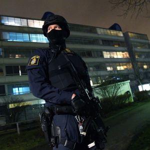 Poliisi seisoo poliisislaitoksen edustalla.
