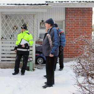 Asukkaat ja rakennustarkastaja rivitalon pihalla