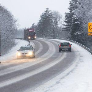 Autoja ajaa talvisella tiellä.