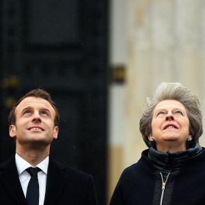 Ranskan presidentti Emmanuel Macron ja Britannian pääministeri Theresa May katsovat ylöspäin.