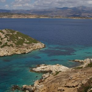 Kartion muotoinen pikkusaari sinisessä meressä, edustajja isomman saaren kalliorantaa.