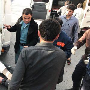 Pommi-iskussa loukkaantunutta miestä siirretään ambulanssiin.