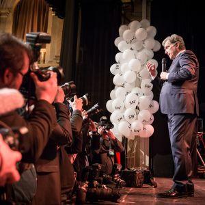Sauli Niinistö lavalla ja lavan edusta on täynnä median valokuvaajia.