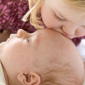 vauva ja isosisko joka pussaa lasta