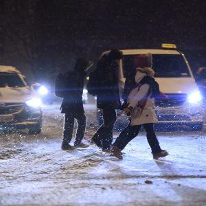 Jalankulkijoita lumisella suojatiellä.