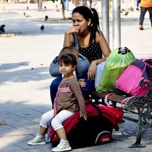 Venezuealalainen äiti ja pieni tyttö istuvat tavaroidensa kanssa puistonpenkillä Kolumbiassa.