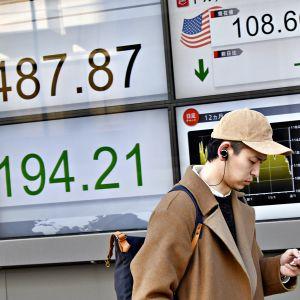 Nuori mies katselee älypuhelintaan Tokion kadulla 6. helmikuuta. Hänen takanaan näkyy laskevia pörssilukemia.