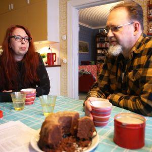 Nainen ja mies kahvipöydässä.