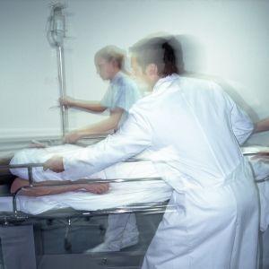 Lääkäri ja sairaanhoitajat työntävät potilasvuodetta kiireellisesti hoitoon.