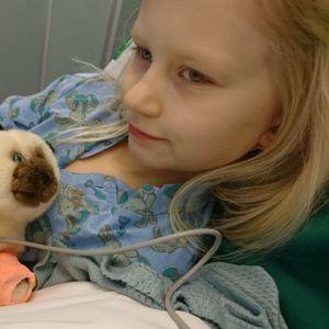 Lapsi makaa sairaalan sängyssä pehmolelu sylissään.