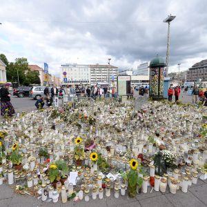 Muistokynttilöitä ja -kukkia elokuun puukotuksen tapahtumapaikalla Turussa.