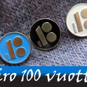 Sininen, musta ja valkea rintamerkki, joissa yhdistyvät numerot 100 ja 18.