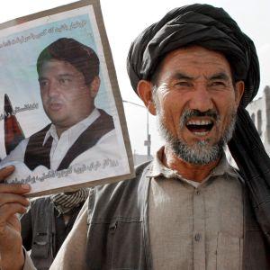 Kuvassa hazaramies pitää oikeassa kädessään taulua, jossa kolmen miehen valokuvat.