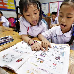Thaimaalaisia lapsia opiskelemassa englantia ala-asteella Bangkokissa.