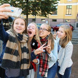 Kuvassa nuoret ottavat älypuhelimella kuvaa itsestään.