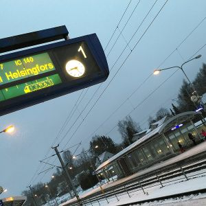 Hämeenlinnan juna-aseman raiteet ja opastaulu, joka kertoo junan olevan myöhässä