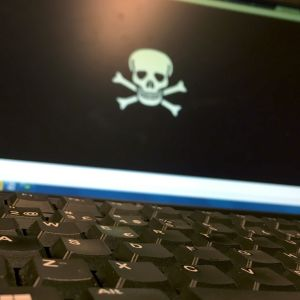 Tietokone, jonka näytöllä on pääkallosymboli.
