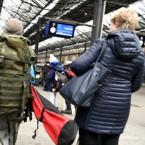Junamatkailijoita Helsingin rautatieasemalla.