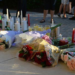 Kukkia ja muistokynttilöitä kadulla.