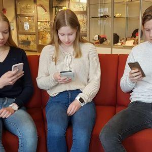 kolme nuorta yhdeksäsluokkalaista kännyköidensä kimpussa