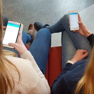 kaksi yläkoululaista katsoo kännyykkäänsä