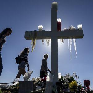 Ihmiset toivat kukkia ja kynttilöitä kouluampumisen uhrien muistoksi Parklandissa Floridassa.