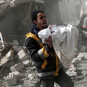 Mies kantaa pommituksissa tuhoutuneen talon raunioista pelastettua vauvaa Itä-Ghoutan Hamourissa.