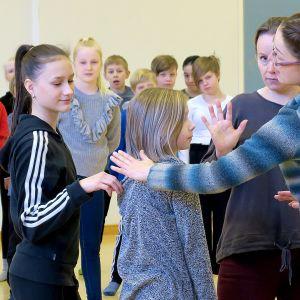 Annan Nora Kansallisoopperasta, Haukkavuoren musiikkiluokkalaisia ohjattavana koulun liikuntasalissa, Ihmepoika A -oopperan harjoitukset