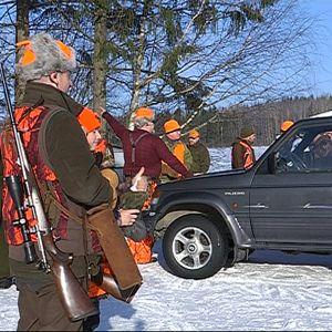 metsästäjiä lähdössä jahtiin, käskynjakoa autojen ympärillä