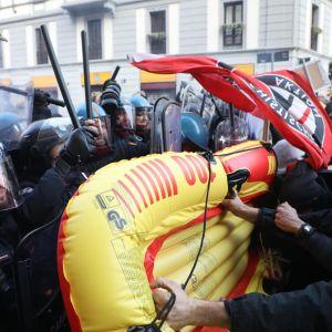 Mellakkapoliisit seisovat suojamuurina poliittisia marssijoita vastaan Milanossa.