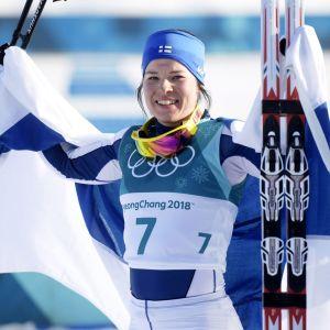 Krista Pärmäkoski juhlii kakkossijaansa Suomen lipun kanssa.