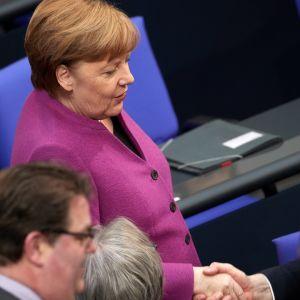 Angela Merkel kättelee Jens Spahnia Saksan parlamentissa 22. helmikuuta.