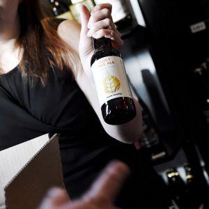 Nainen esittelee olutpulloa panimokaupassa.
