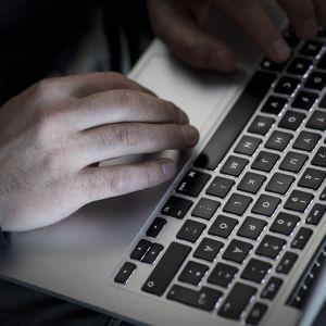 Miehen kädet kannettavan tietokoneen näppäimistöllä.