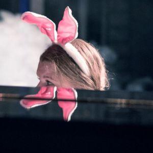 Nainen pianon takana kanin korvat päässä