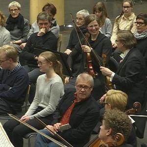 Yleisö istuu orkesterin keskellä konsertissa