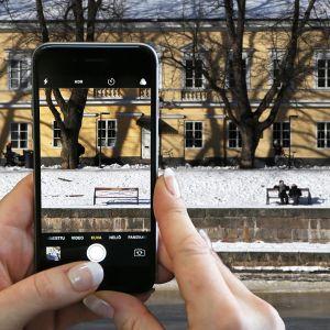 Nainen ottaa Turun Aurajoen maisemasta valokuvan älypuhelimella.