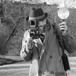 Toimittaja Nopsanen (Pentti Siimes) työssään elokuvassa Tähdet kertovat, komisario Palmu.