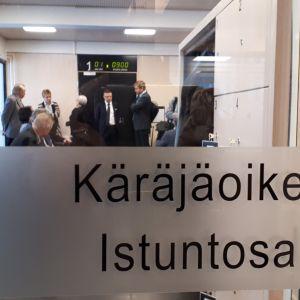 Ylivieska-Raahen käräjäoikeuden istustosalin lasiovi, jonka takana henkilöitä odottamassa pääkäsittelyn alkua.