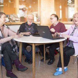 """Anja Tyrjy (vas.), Touko Virkkala ja Reetta Siermala ovat saapuneet SeniorSurffaukseen omien teknisten ongelmiensa kanssa. """"Laitteilla leikkimällä sitä oppii"""", sanoo Håkan Björkström (kesk. oik.), joka auttaa ikätovereitaan surffailemaan kehityksen aallonharjalla."""
