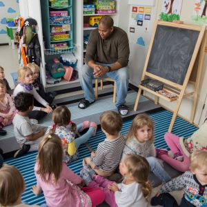 Lapsia istumassa leikkihuoneen matolla päiväkoti Laugh&Learnissa.
